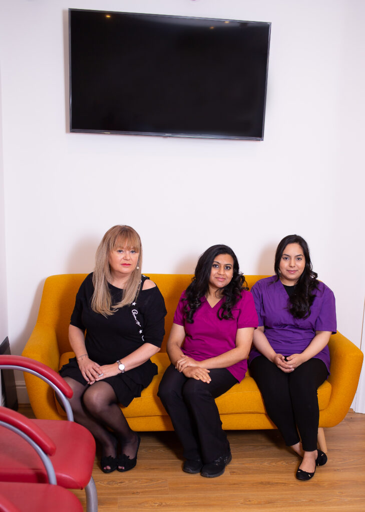Three women sitting on a yellow sofa